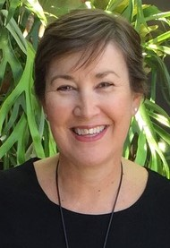 Headshot of Deb Turner wearing a black top standing in front of a green plant background
