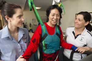 two physiotherapists assisting a women in a harness learning to walk again