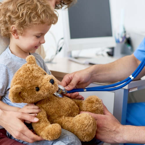Blond child holding a teddy bear while clinician uses a stethascope on the bear